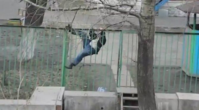 Ryskt fyllo försöker klättra över ett staket